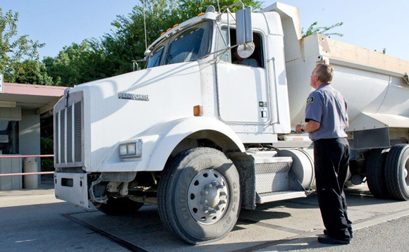 CIS Security guard at checkpoint for industrial plant, with large truck.